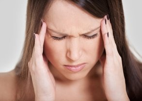 woman holding head pain headache migraine